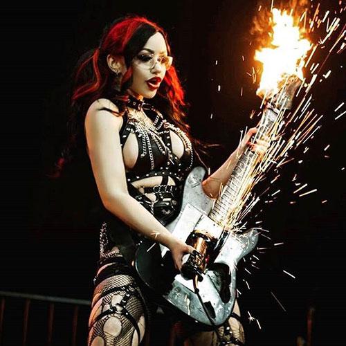 Dani Divine angle grinding a guitar.